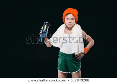 Confident sporty boy with towel on neck holding sports bottle with water isolated on black Stock photo © LightFieldStudios