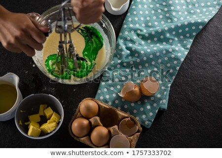 Woman whisking batter after adding green food color Stock photo © wavebreak_media