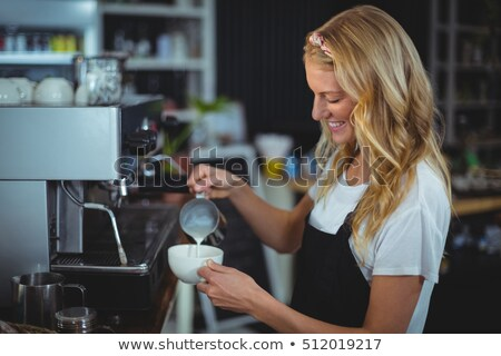 Waitress making cup of coffee at counter in cafe Stock photo © wavebreak_media