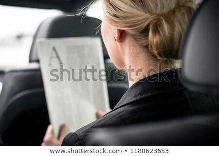 Rear view of businesswoman reading newspaper in car Stock photo © Kzenon