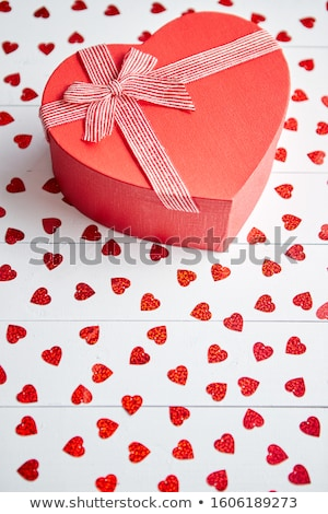 Boxed gift placed on heart shaped red sequins on white wooden table Stock photo © dash