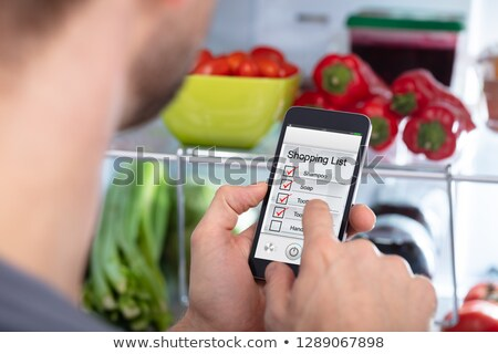 Man Marking Shopping List On Mobile Phone Stock photo © AndreyPopov
