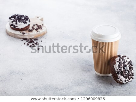 Cardboard coffee cup with black cookies doughnuts on stone kitchen table background. Cafe drink and  Stock photo © DenisMArt