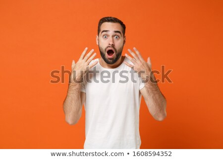 portrait of a shocked young man wearing shirt stock photo © deandrobot