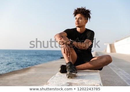 Concentrado jovem cara sessão ao ar livre Foto stock © deandrobot