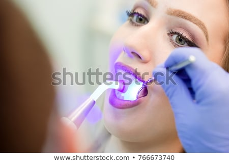 Dentist doing a dental treatment on a female patient. Stock photo © artfotodima