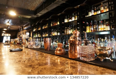 classic bar counter with bottles in blurred background stock photo © dashapetrenko