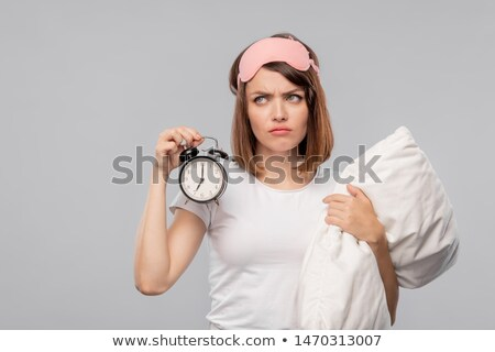 Displeased young woman with pillow holding alarm clock showing 7 am Stock photo © pressmaster