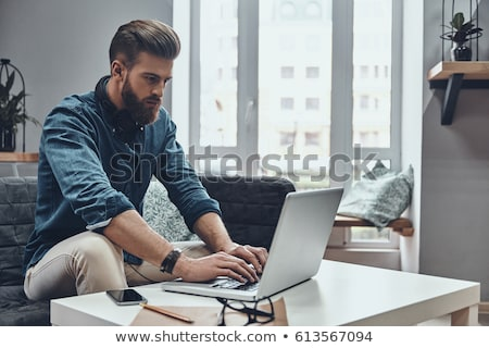 Young man networking or surfing in the net for new creative ideas Stock photo © pressmaster