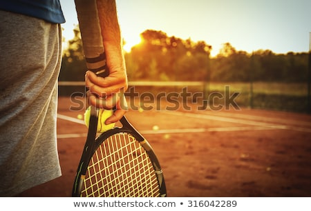 smiling young man with tennis racket Stock photo © dolgachov