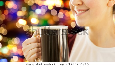 Stock photo: close up of smiling woman with dark beer in mug