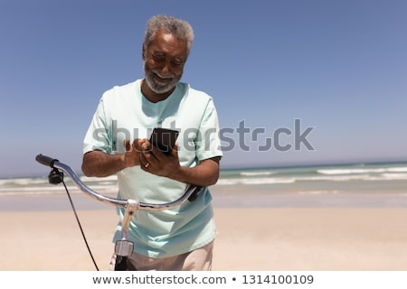 Front view of happy senior man with bicycle using mobile phone on beach in the sunshine Stock photo © wavebreak_media