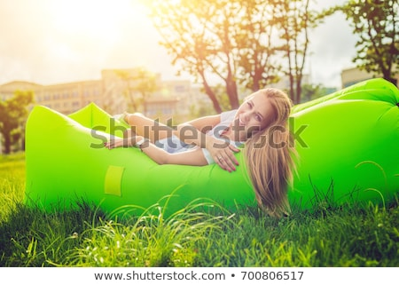 Young woman resting on an air sofa in the park. Stock photo © galitskaya