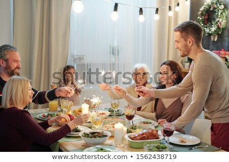 Young and mature adults holding sparkling bengal lights over served table Stock photo © pressmaster