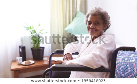 Portrait of happy senior mixed race woman smiling while sitting on bed at nursing home Stock photo © wavebreak_media