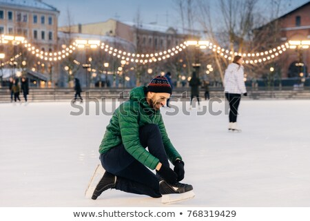 Stock photo: Portrait Of Cheerful Male Laces Up Skates As Going To Go Skating