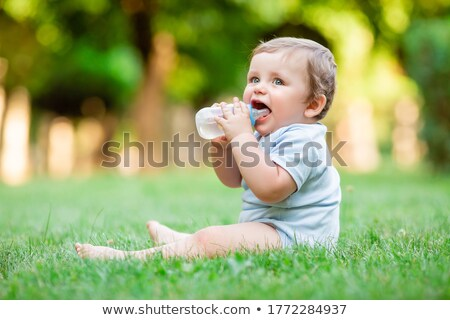 Boy and girl sit on grass and drink from bottle Stock photo © Paha_L