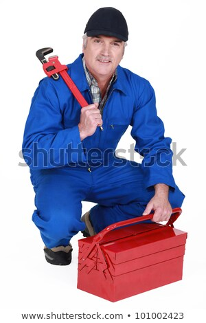 Stock photo: craftsman kneeling holding a spanner
