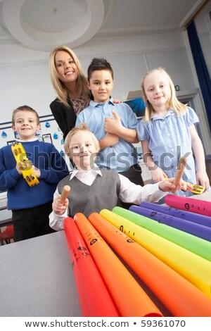 Group Of Primary Schoolchildren And Teacher Having Music Lesson  Stock photo © monkey_business