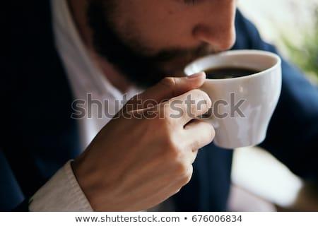 férfi · iszik · kávé · iroda · mosolyog · ül - stock fotó © deandrobot
