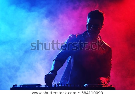 DJ playing music at mixer on colorful foggy background Stock photo © deandrobot