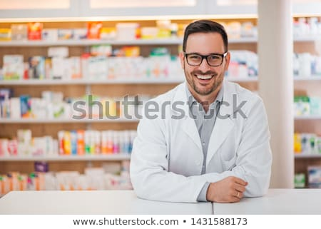 Pharmacist man with medicine at counter in pharmacy Stock photo © vectorikart