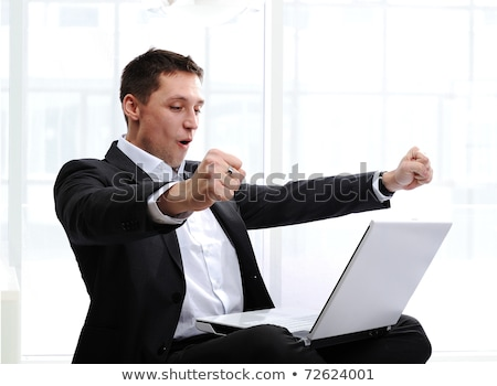Happy executive raising fists in excitement, in front of laptop Stock photo © zurijeta