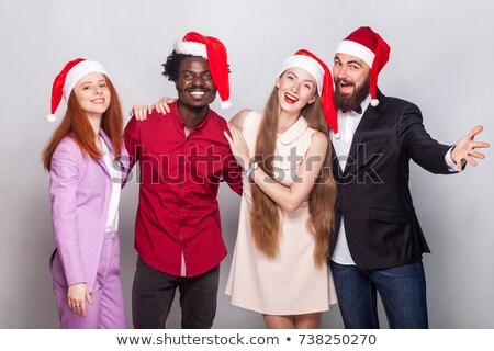 friends in santas hats looking at camera stock photo © deandrobot