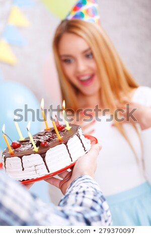 Young girl wearing party hat with cake in front of her smiling Stock photo © monkey_business