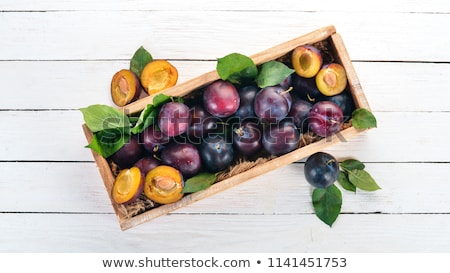 Fresh plums with green leaves on wooden rustic background, top view Stock photo © yelenayemchuk