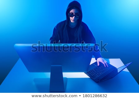 Hooded computer hacker working on desktop PC computer Stock photo © stevanovicigor