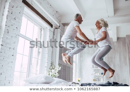 Woman jumping on bed smiling stock photo © monkey_business
