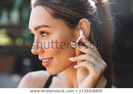 Portré fiatal fitnessz lány fülhallgató ül Stock fotó © deandrobot