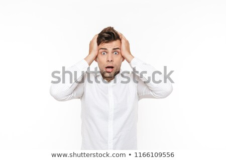 Portrait of uptight nervous man grabbing his face in confusion a Stock photo © deandrobot