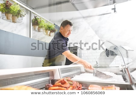 male seller adding ice to fridge at fish shop Stock photo © dolgachov