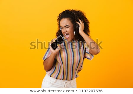 Woman posing isolated over yellow background listening music with headphones dancing singing. Stock photo © deandrobot