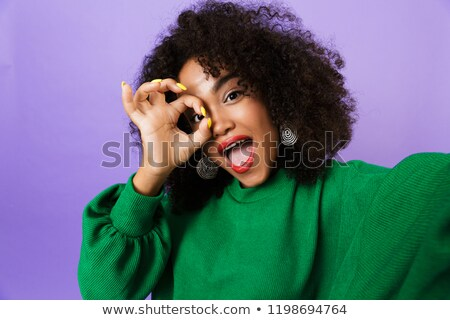 Woman isolated over violet background showing okay gesture take selfie by camera. Stock photo © deandrobot