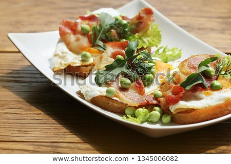 Bruschetta with rucola, chrispy bacon and poached egg served on white plate stock photo © Virgin