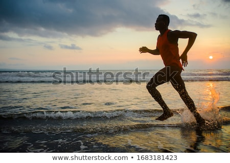 young man exercising on beach stock photo © andreypopov