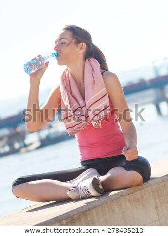 Komoly fiatal sportok nő ül kint Stock fotó © deandrobot