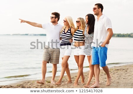 friends in striped clothes walking along beach Stock photo © dolgachov