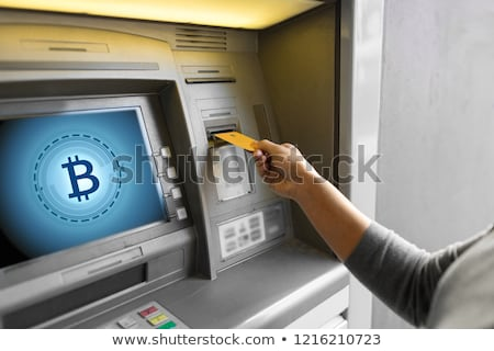 woman at atm machine with bitcoin icon on screen stock photo © dolgachov