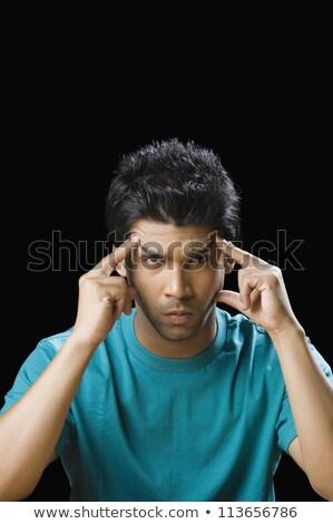 indian man touching his temples Stock photo © dolgachov