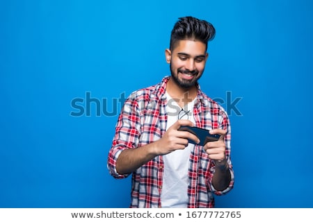 happy indian man playing game on smartphone Stock photo © dolgachov