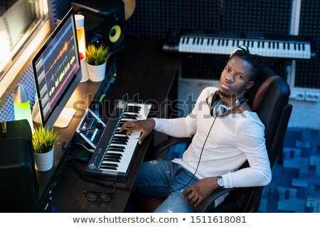 Young Afroamerican man in casualwear looking at you while sitting in studio Stock photo © pressmaster