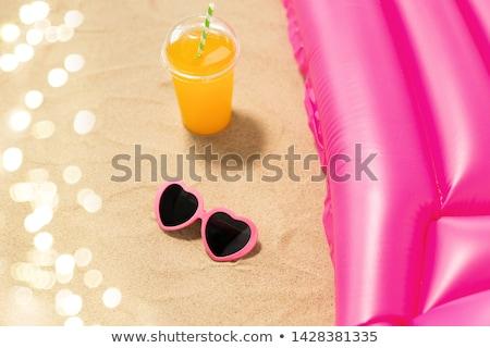 sunglasses, juice and pool mattress on beach sand Stock photo © dolgachov