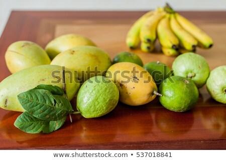 Fruits on the wooden table. Mangoes, bananas, tangerines, guava Stock photo © galitskaya