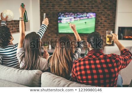 friends with beer and popcorn watching tv at home Stock photo © dolgachov