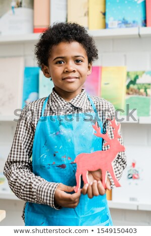 happy african schoolboy in blue apron holding handmade deer stock photo © pressmaster