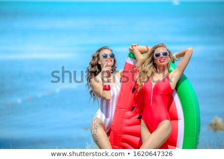 Two girl girlfriends stand on the beach next to a large inflatable watermelon Stock photo © ElenaBatkova